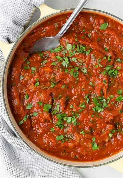Imagen de una olla grande de salsa de espagueti casera con una cuchara. Se adorna con mucho perejil fresco picado.