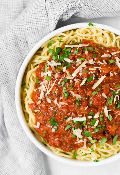 Imagen de espagueti con salsa casera. El plato de espagueti está adornado con queso parmesano y perejil fresco.