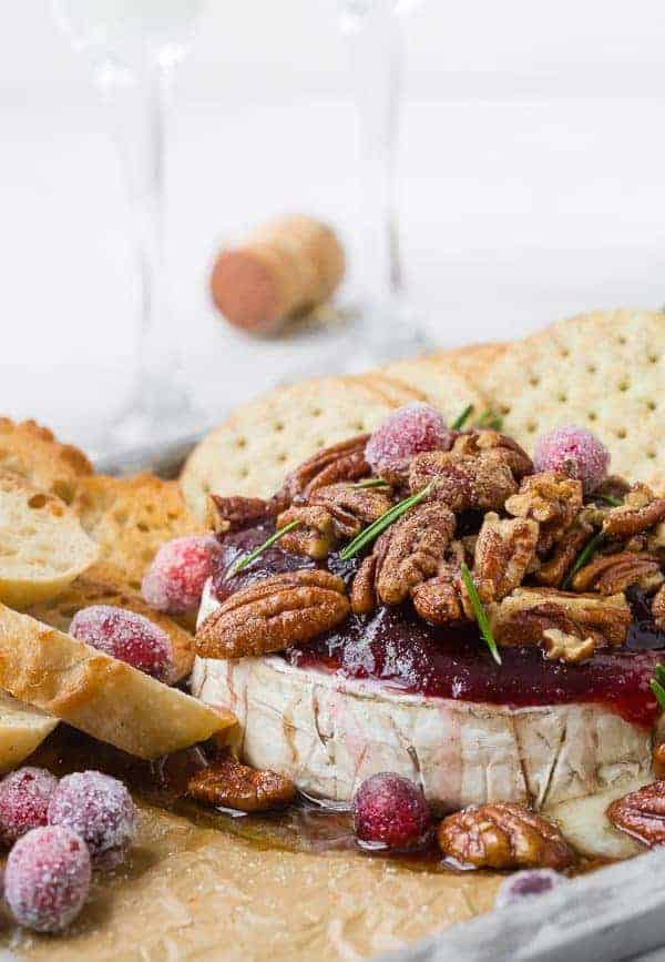Baked Brie Recipe Image with Cranberries and Bourbon Candied Walnuts. Decorated with sugared cranberries and rosemary.