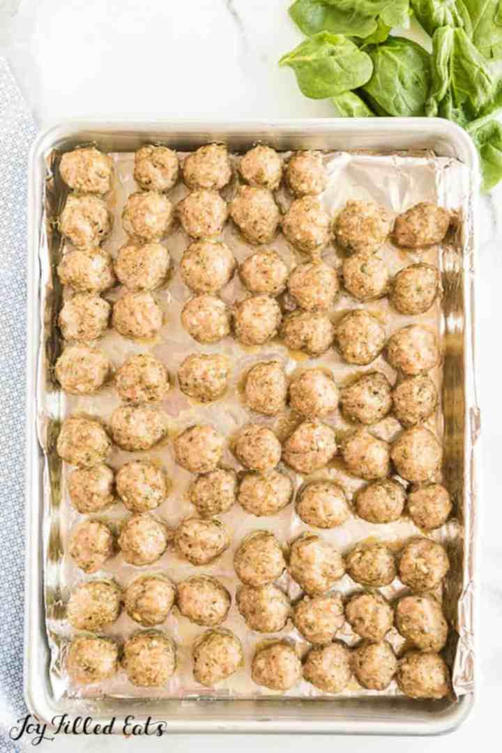 Mini cooked meatballs on a baking sheet for Italian wedding soup