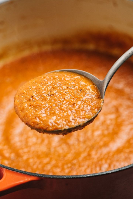 Salsa marinara en un cucharón encima de una olla