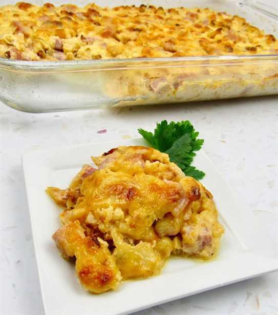 Rodaja de coliflor asada y jamón a la cazuela en un plato con cazuela en segundo plano.
