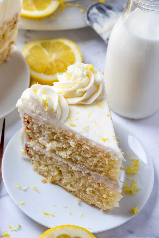 Rebanada de pastel de limón en la placa blanca foto aérea mostrando la parte superior con limones y leche en segundo plano.