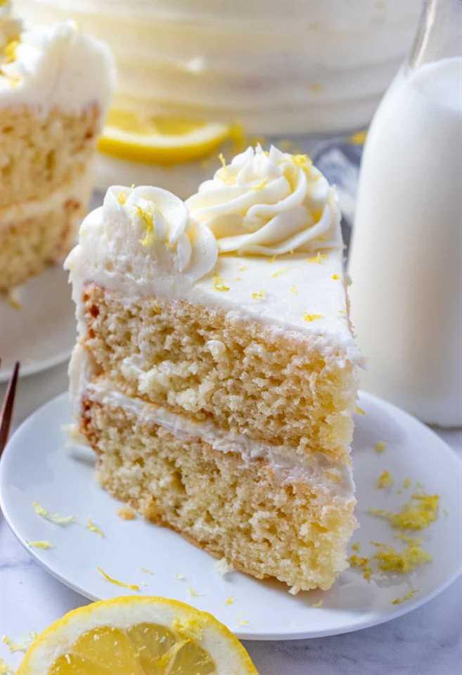 Corte el pedazo de pastel en un plato blanco con leche en el fondo y la ralladura de limón en el plato