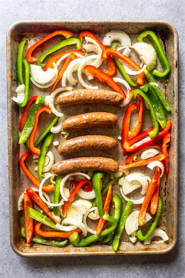 Pimientos crudos, cebollas y salchichas en una sartén antes de ir al horno.