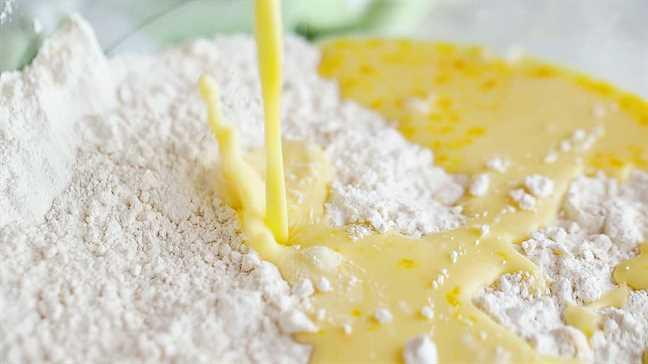 Verter los ingredientes húmedos en seco para hacer bollos.
