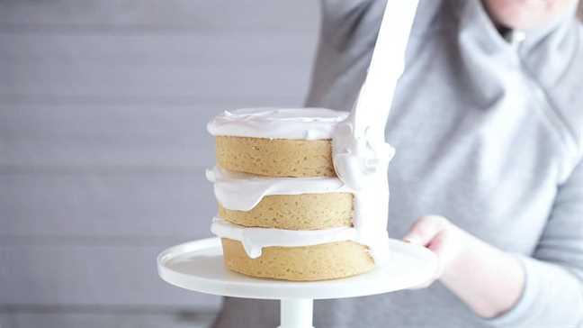 Glaseado de un pastel de coco con glaseado de malvavisco.