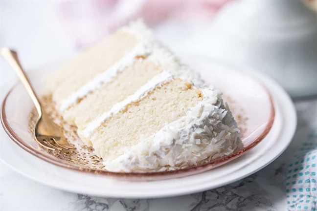 La mejor receta de pastel de coco, horneado y glaseado con glaseado de malvavisco y coco, cortado en rodajas y servido de lado.