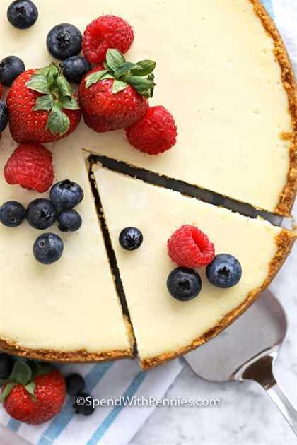 Imagen de arriba de tarta de queso con bayas en la parte superior, con pieza cortada