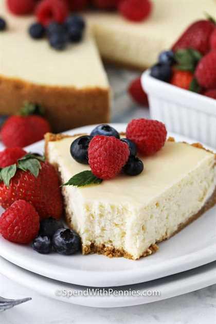 Ciérrese para arriba del pastel de queso en una placa con las bayas en el top y una mordedura tomada de él.