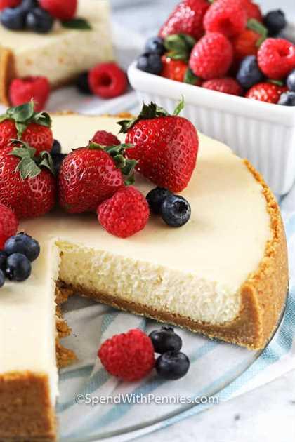Ciérrese para arriba del pastel de queso cubierto con las bayas, con un pedazo sacado de él.