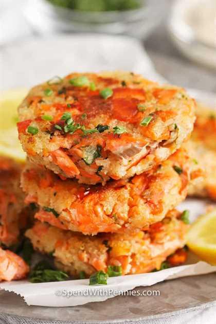 Ciérrese para arriba de las croquetas de color salmón en una pila, adornadas con perejil.