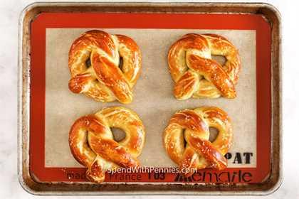 Cuatro pretzels suaves horneados en una bandeja para hornear.