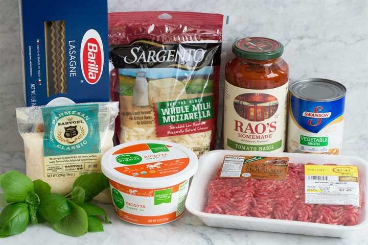 Imagen que muestra los ingredientes utilizados para hacer una lasaña fácil. Incluye fideos de lasaña, parmesano, albahaca, ricota, mozzarella, marinara embotellada, carne molida y caldo de verduras.