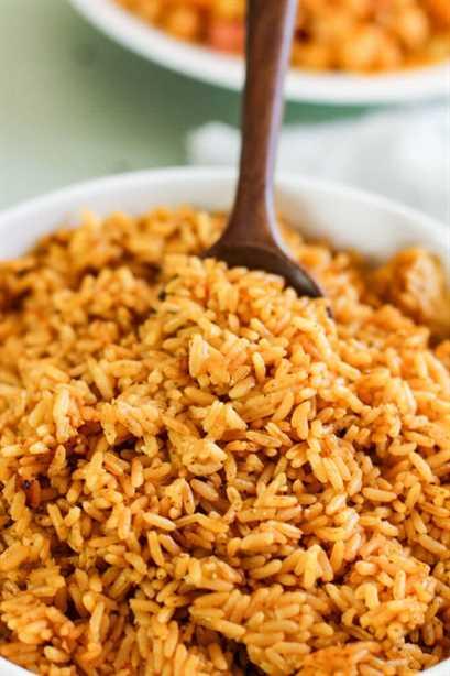 cuchara de madera en el centro del tazón blanco lleno de arroz amarillo