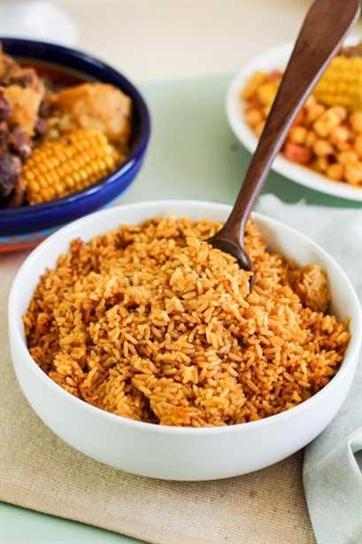 Mesa con arroz amarillo en un tazón blanco y un tazón azul con rabo de buey estofado y mazorca de maíz.
