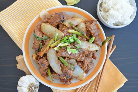 Carne mongol en un plato con palillos