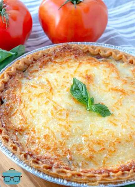 totalmente cocido, pastel de tomate con tocino cubierto con una ramita de albahaca fresca con tomates enteros representados en el fondo