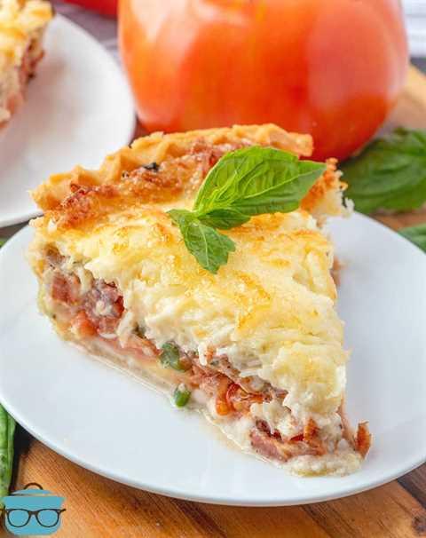Rebanada, tarta de tomate y tocino con queso derretido, en un plato blanco