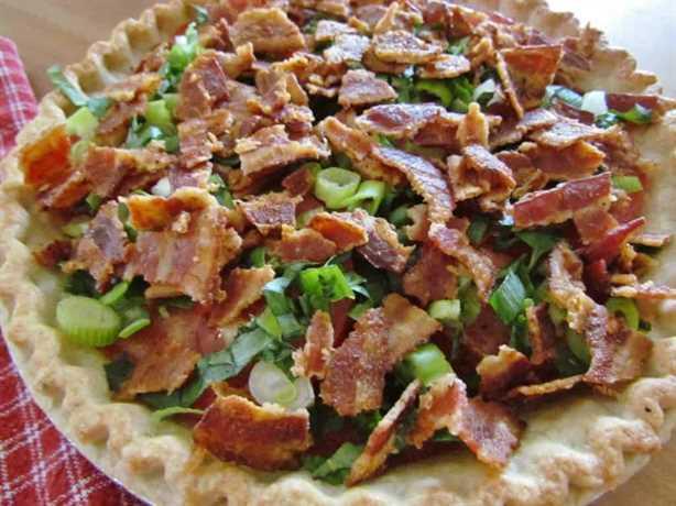albahaca en rodajas, cebolla verde y tocino cocido y desmenuzado en capas sobre tomates en rodajas en una corteza de tarta