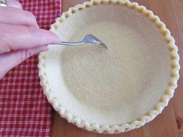 usando un tenedor para hacer agujeros en una masa de pastel congelada