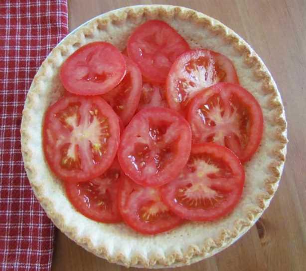 rodajas de tomate en capas en el fondo de una corteza de pastel parcialmente cocida