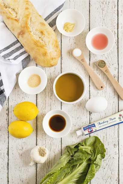 Todos los ingredientes individuales para hacer la ensalada Casear en una pizarra blanca