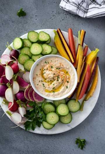 receta de hummus de frijoles blancos presentada en una bandeja con verduras frescas
