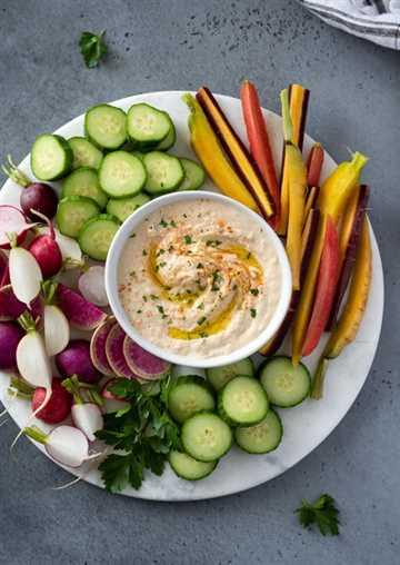 Fotografía cenital de hummus de judías blancas en una fuente de servir con verduras