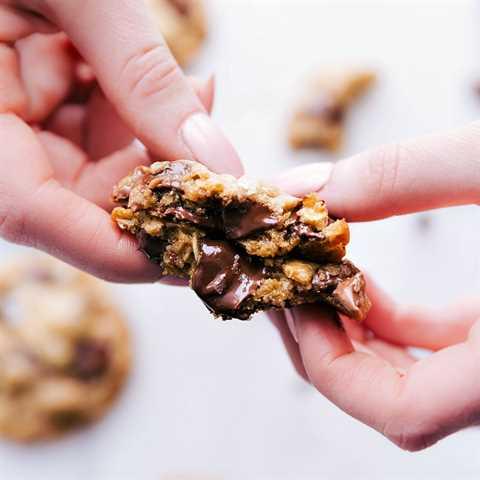 Imagen de una de las galletas de chispas de chocolate de mantequilla marrón recién salidas del horno cortadas por la mitad mostrando la pegajosa dentro