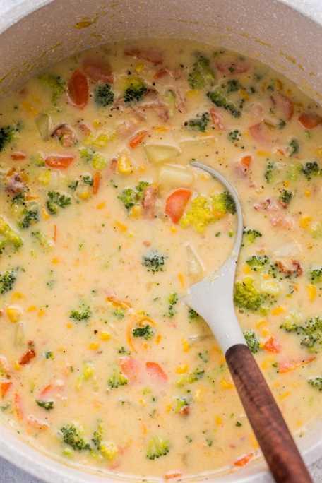 Sopa de verduras en un horno holandés cargado de verduras y un cucharón lleno de sopa.
