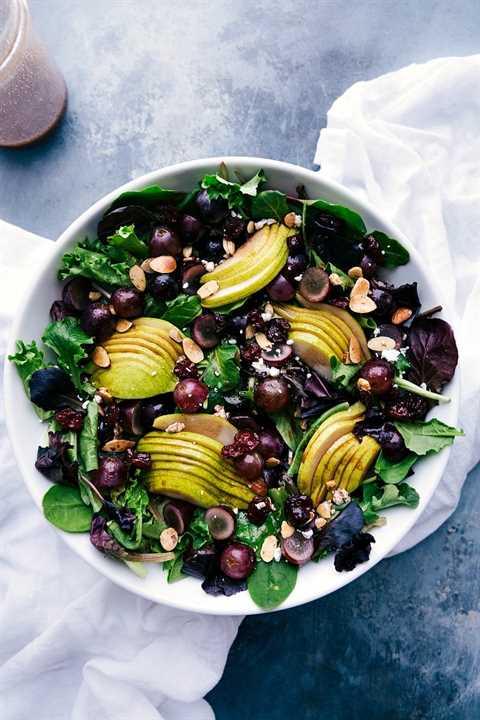 Imagen de arriba de la ensalada de pera, uva y cereza verde con el aderezo balsámico de cereza a un lado