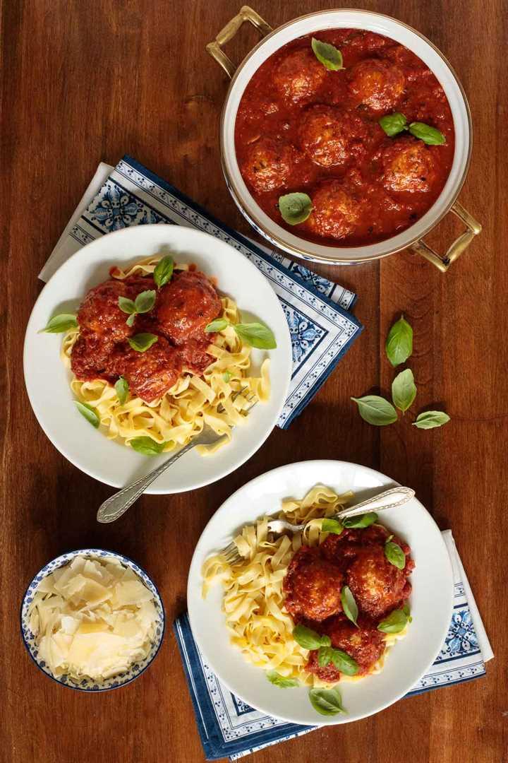 Fotografía aérea de una olla y dos tazones de albóndigas de pollo italianas y marinara con pasta y queso parmesano rallado.