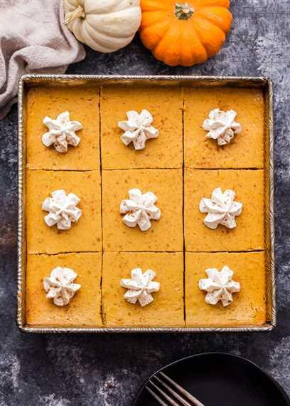 Barras cremosas de pastel de calabaza en moldes cuadrados de metal cubiertos con crema batida.
