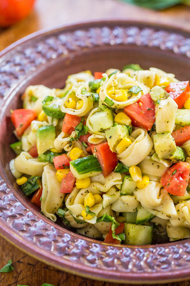 Fresh Garden Tortellini pasta salad: juicy tomatoes, cucumbers and corn with creamy avocado, basil and parmesan, mixed with lemon vinaigrette and cheese tortellini. Healthy, easy, ready in 15 minutes!