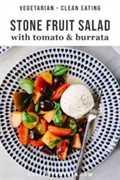 Una porción de ensalada de fruta de hueso con tomate y queso burrata en un plato azul y blanco.