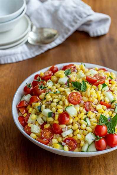 La ensalada de maíz fresca y brillante está llena de maíz fresco, tomate, pepino y albahaca. Es la guarnición perfecta y refrescante.