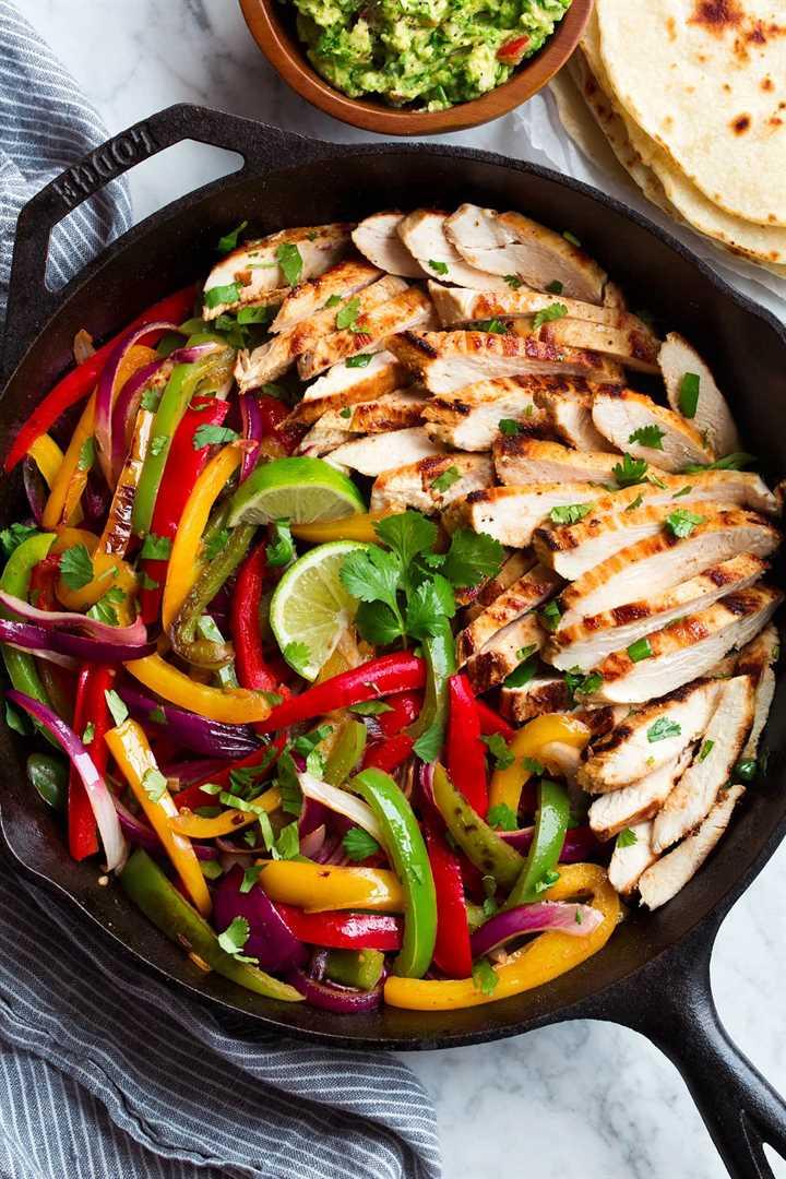 Mezcla de fajitas de pollo en una sartén de hierro fundido. Mostrando pechugas de pollo en rodajas, pimientos y cebollas. Las tortillas y el guacamole se sirven al lado.