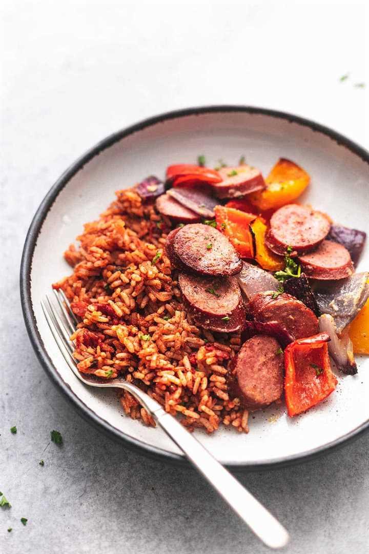 salchichas y verduras y arroz en un plato con un tenedor