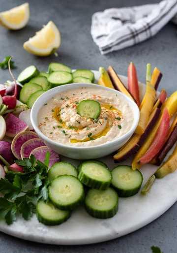hummus de judías blancas en una fuente para servir rodeado de verduras frescas