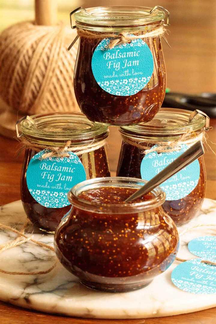 Foto vertical de Balsamic Fig Jam en frascos de vidrio con etiquetas de regalo azules.