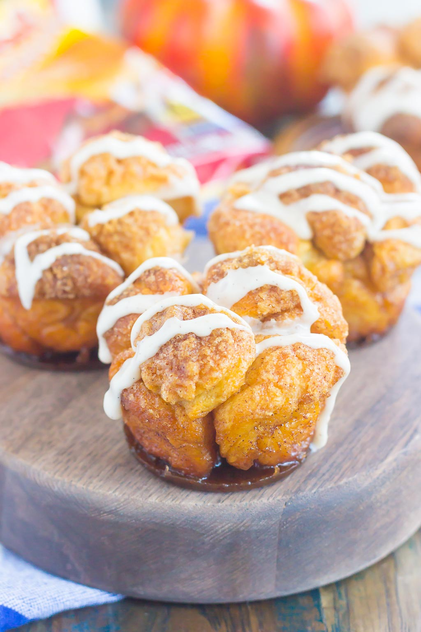 Estas magdalenas de pan de mono de calabaza y especias son un regalo simple que es perfecto para el desayuno o el postre. La masa prefabricada se enrolla en una acogedora mezcla de especias de calabaza y luego se hornea en moldes para muffins. Cubierto con un dulce glaseado de calabaza y excelente para las vacaciones, ¡este muffin pegajoso seguramente impresionará a todos! #monkeybread #monkeybreadrecipe #pumpkinmonkeybread #pumpkindessert #dessert #falldessert #pumpkinrecipe