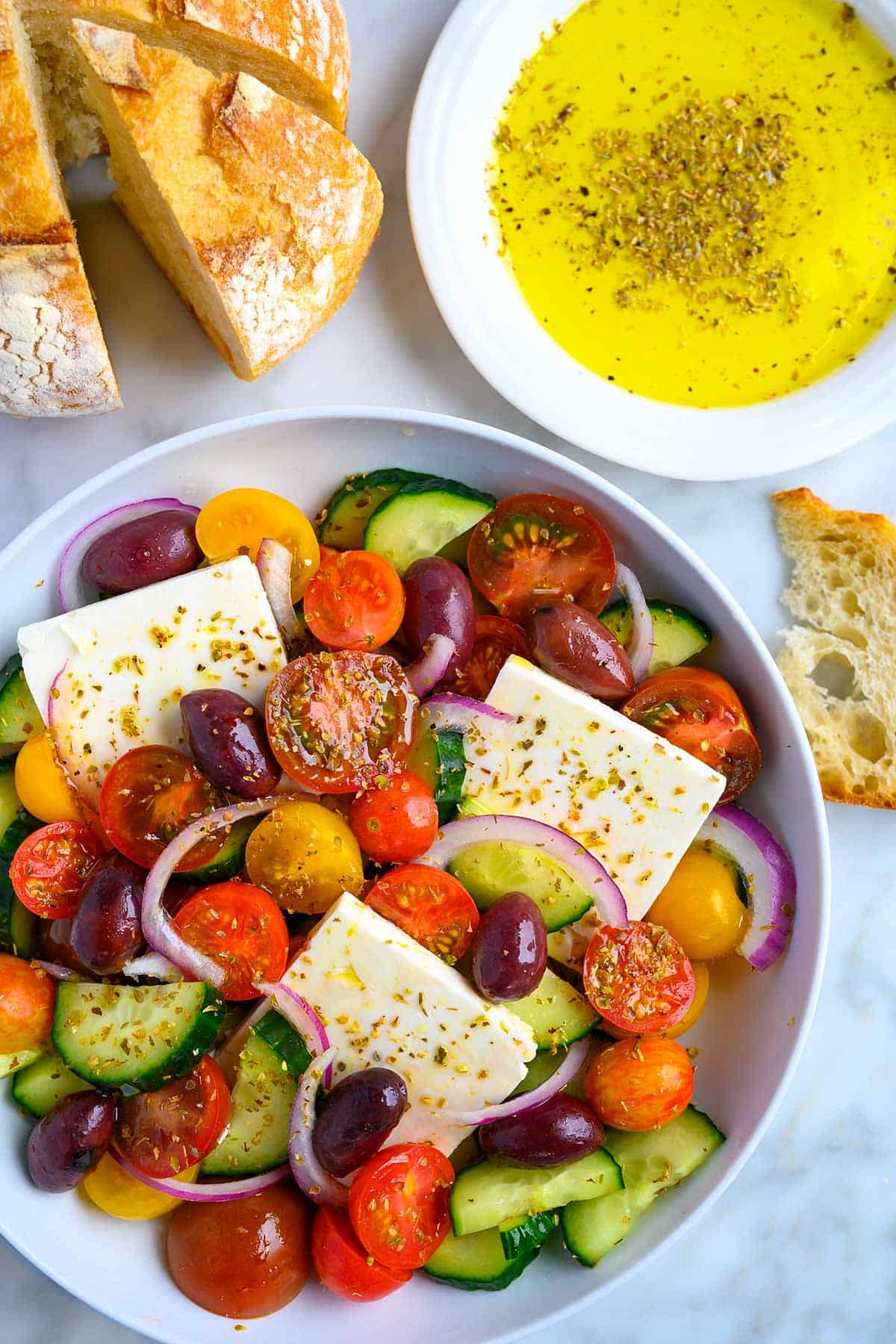 Bowl full of a Greek salad with bread and dipping oil on the side.