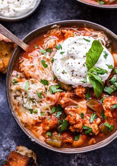 Olla de cocción lenta Italiano Pavo Chile en un recipiente cubierto con queso ricotta y mozzarella. Baguette trozos al lado del tazón.