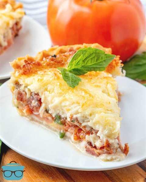 Tarta de tomate y tocino con mozzarella derretida servida en un plato blanco con una ramita de albahaca encima
