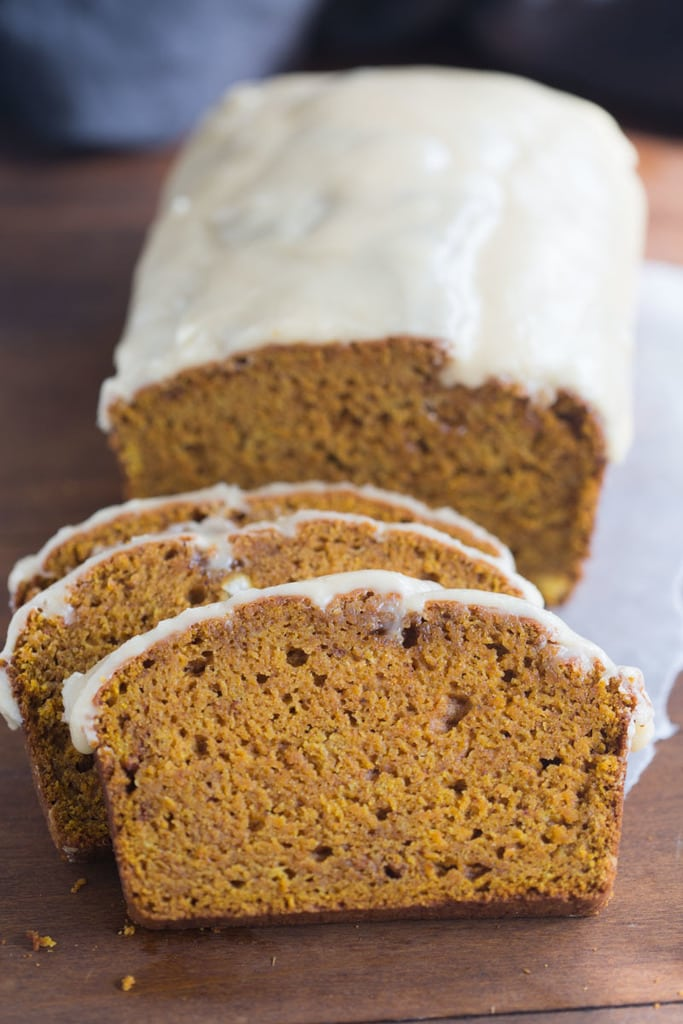 Pumpkin bread with brown butter maple frosting and three cut slices.