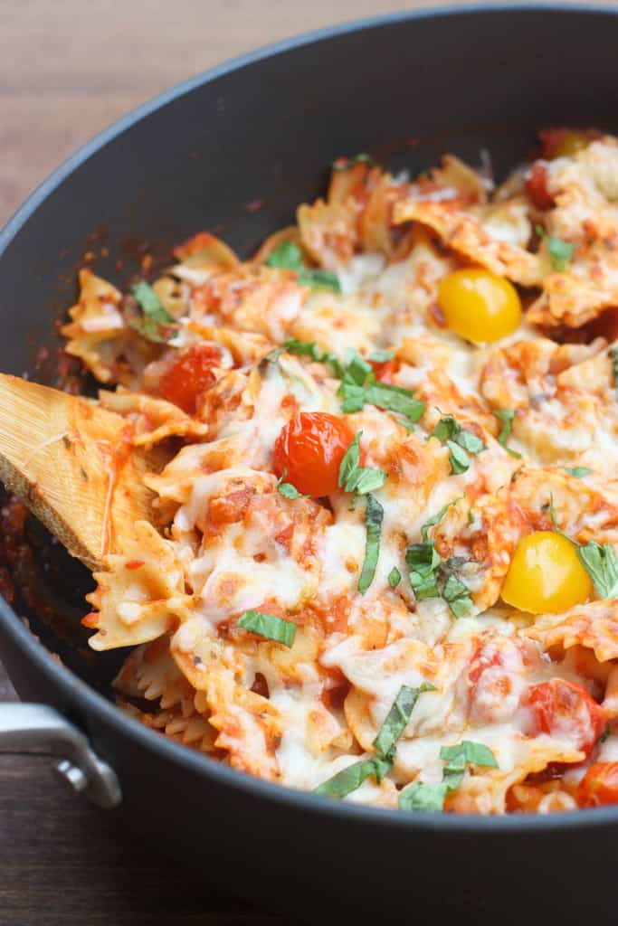 A frying pan filled with chicken mozzarella pasta and a wooden spoon scooping out one tablespoon.