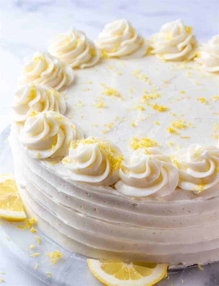 Pastel de limón decorado en un plato giratorio con remolinos, rodajas de limón y ralladura de limón en la parte superior