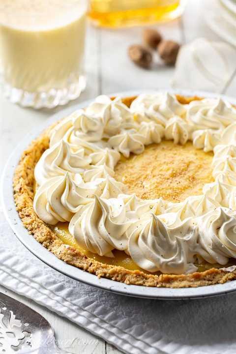 Un pastel cremoso de ponche de huevo cubierto con crema batida y nuez moscada rallada fresca