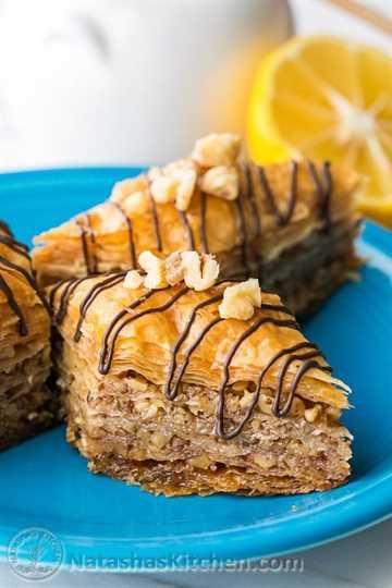 Piezas de baklava cargadas de nueces y miel de miel con guarnición de chocolate: una vista de corte central de esta receta casera de baklava que muestra capas tiernas, crujientes y tiernas.